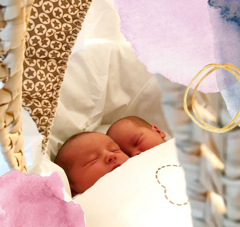 Twin babies asleep in a Moses basket