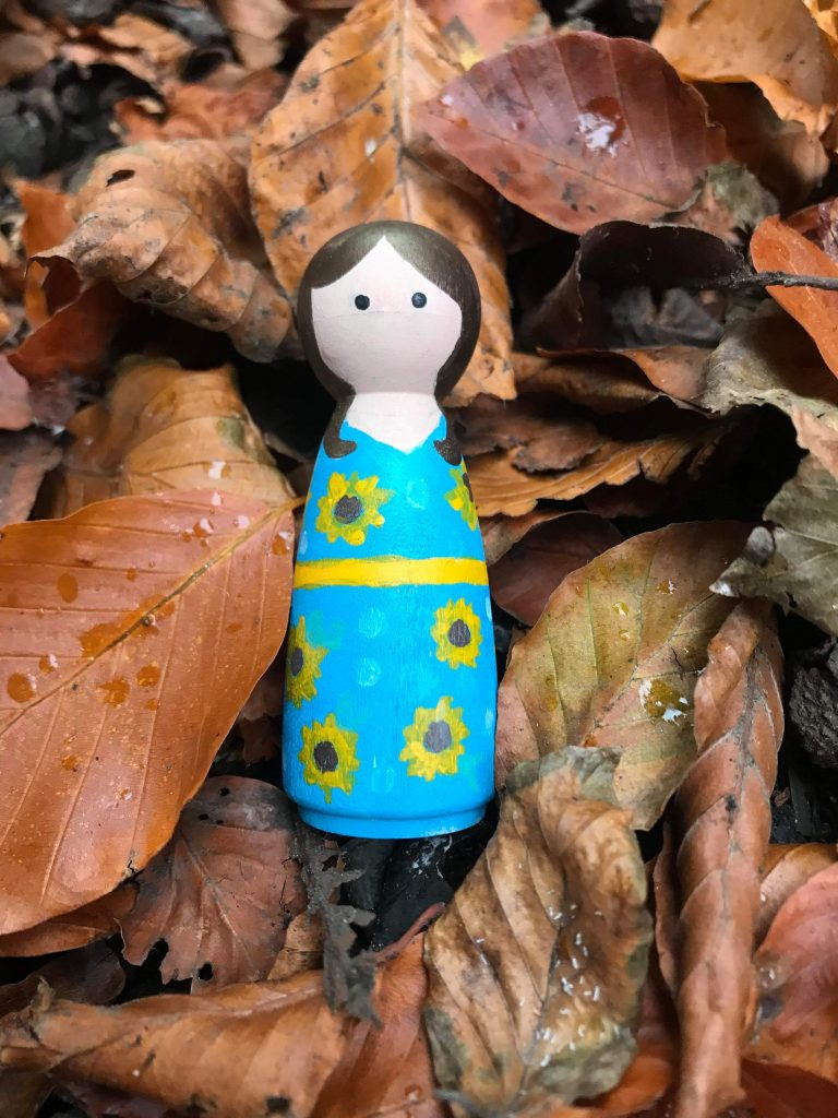 A peg doll laying on a bed of autumnal leaves.